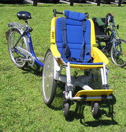 Blue and yellow front seat which straps someone in, with a blue bike attached in the back to pedal