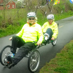 Two seniors in yellow jackets riding a tandem trike