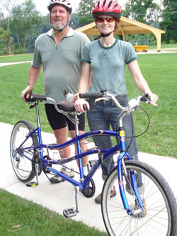 Two people holding up a tandem bicycle and smiling