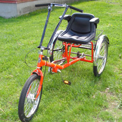Orange trike with seat with extra padding and stability and long handlebars