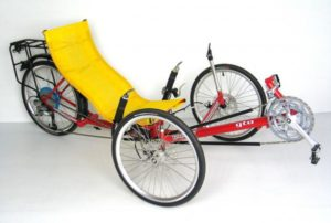 A yellow seated trike with a red frame.