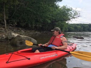 A man with a hat sits in a red kayak, holding a paddle with yellow blades