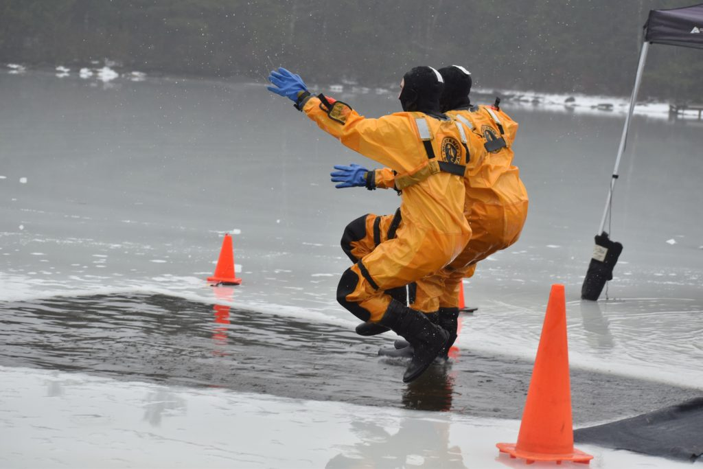 2 men dressed in yellow dry suits in mid air jumping into plunge hole