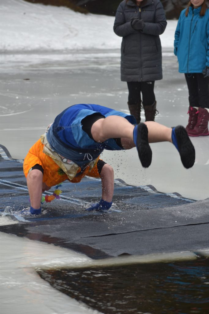 A woman in blue shorts and orange shirt stands on her hands with feet toward the plunge hole