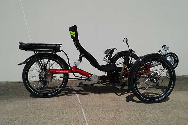 electric recumbent trike. color red with black seat. two wheels in front with recumbent seat and one wheel in back.