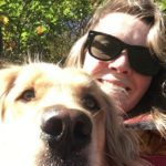 A woman with sunglasses smiling with a golden retreiver dog