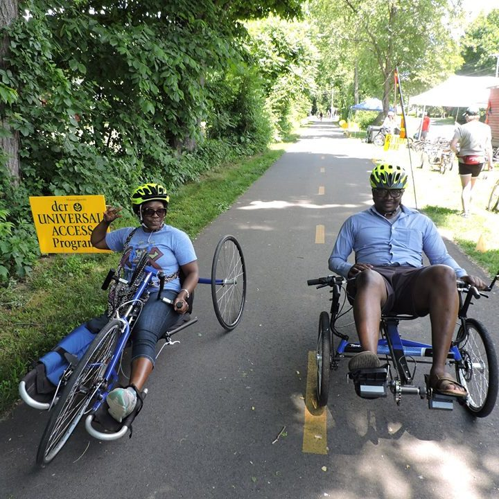 2 people, smiling, one on a handcycle and one on a recumbent trike